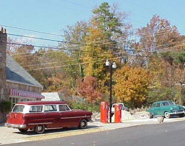 Closer view of antique cars and gas pumps